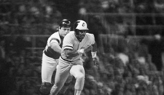 Chicago White Sox catcher Carlton Fisk, left, chases Baltimore Orioles Al Bumbry toward first base after a dropped third strike in the first inning of Game 3 of the American League playoffs in Chicago, Oct. 7, 1983. Fisk tagged Bumbry out. (AP Photo/Bob Daugherty) **FILE**