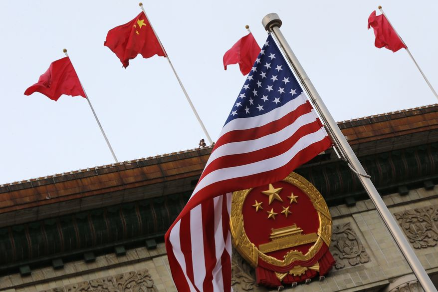 An American flag is flown next to the Chinese national emblem and flags during a welcome ceremony for visiting U.S. President Donald Trump outside the Great Hall of the People in Beijing, Thursday, Nov. 9, 2017. President Donald Trump sought to present a united front with Chinese President Xi Jinping following two days of meetings Thursday, despite lingering differences over trade and North Korea. (AP Photo/Andy Wong)