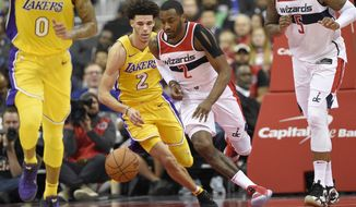 Washington Wizards guard John Wall (2) chases the ball past Los Angeles Lakers guard Lonzo Ball (2) during the second half of an NBA basketball game, Thursday, Nov. 9, 2017, in Washington. Also seen are Lakers forward Kyle Kuzma (0) and Wizards forward Markieff Morris (5). The Wizards won 111-95. (AP Photo/Nick Wass)