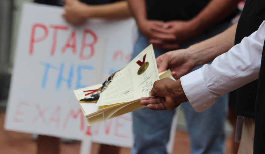 Inventors marched on the U.S. Patent and Trademark Office's Alexandria headquarters, holding signs and burning their patents in August 2017. Inventors say the rulings often seem arbitrary and are particularly irked by what they see as a pro-corporate bent among the administrative law judges. (Photograph by Elizabeth Malone)
