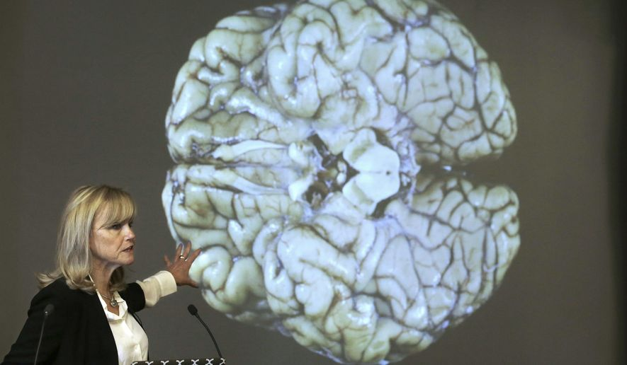 Ann McKee, director Boston University's center for research into the degenerative brain disease chronic traumatic encephalopathy, or CTE, addresses an audience on the school's campus Thursday, Nov. 9, 2017 about the study of NFL football player Aaron Hernandez's brain, projected on a screen behind, in Boston. McKee says Hernandez suffered severe damage to parts of the brain that play an important role in memory, impulse control and behavior. (AP Photo/Steven Senne) ** FILE **
