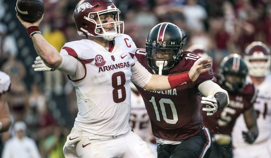 FILE - In this Oct. 7, 2017, file photo, Arkansas quarterback Austin Allen (8) attempts a pass as South Carolina linebacker Skai Moore (10) rushes in during the second half of an NCAA college football game in Columbia, S.C. Allen is healthy and appears ready to play again after missing the last four games with a shoulder injury. That doesn't mean for sure he will play Saturday against LSU, however, with Razorbacks coach Bret Bielema keeping his options open with freshman Cole Kelley. (AP Photo/Sean Rayford, File)