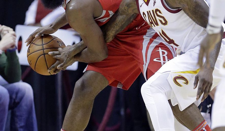 Houston Rockets guard James Harden (13) keeps the ball from the reach of Cleveland Cavaliers guard Iman Shumpert (4) during the first half of an NBA basketball game Thursday, Nov. 9, 2017, in Houston. (AP Photo/Michael Wyke)