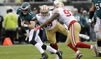 "FILE - In this Oct. 29, 2017, file photo, San Francisco 49ers linebacker Dekoda Watson (97) and defensive end Solomon Thomas (94) try to take down Philadelphia Eagles quarterback Carson Wentz (11) during the first half of an NFL football game in Philadelphia. Lopsided wins have been common during Philadelphia's seven-game winning streak. The average margin of victory is 14 points, including three wins by at least 23 points. The biggest victory--51-23 over the Denver Broncos--sent the Eagles into their off week convinced they have something special. Yet, they even nit-pick dominant performances. That's one sign of an elite team. ""We'll never settle, there's always things to learn from,"" Wentz said. (AP Photo/Michael Perez, File)"