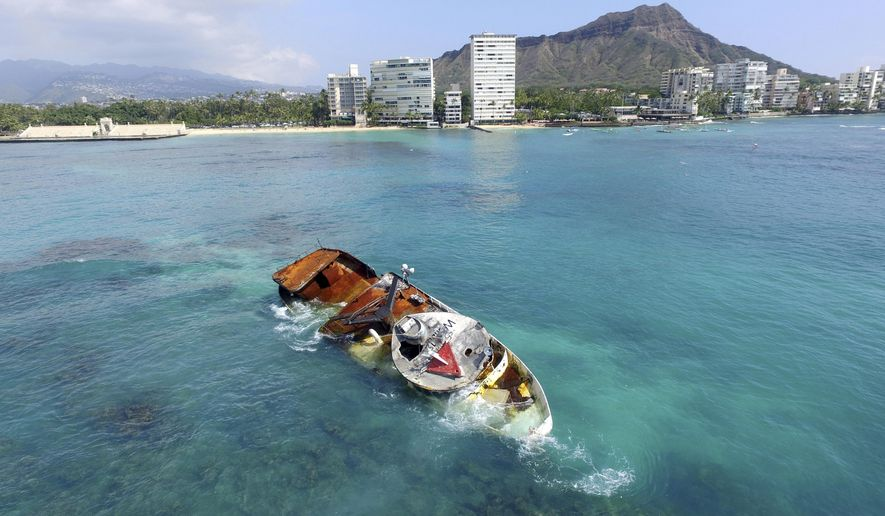 This Nov. 1, 2017 drone photo shows the fishing boat Pacific Paradise, leaking oil and diesel fuel just offshore of hotels on Waikiki's pristine white sand beaches with Diamond Head in the background in Honolulu. The fishing boat transporting foreign workers destined for low-paying jobs in Hawaii's fishing fleet smashed into a shallow reef last month. The crash of the 79-foot (24-meter) boat illustrates a potential environmental impact of the Hawaii fishing fleet's practice of transporting foreign workers by boat. (Carroll Cox via AP)