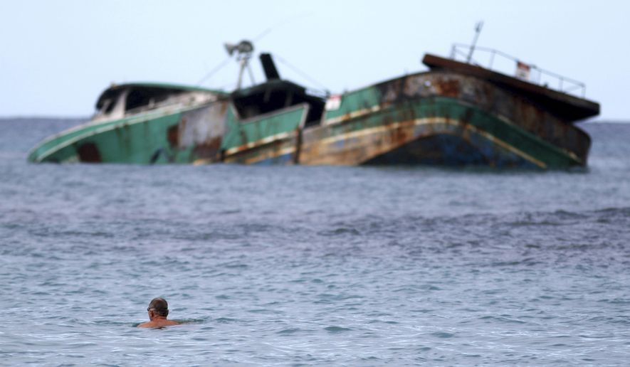 In this Wednesday, Nov. 8, 2017 photo, a swimmer looks at the Pacific Paradise, a commercial fishing vessel that ran aground about a month ago off Kaimana Beach in Honolulu. The fishing boat, which was transporting foreign workers to Hawaii when it smashed into a shallow reef just off the shores of Waikiki, has been leaking oil and fuel into the ocean as beachgoers swim nearby. (AP Photo/Caleb Jones)
