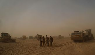 In this Monday, Nov. 6, 2017 photo, U.S. Marines build a military site during a sandstorm in western Anbar, Iraq. The US-led coalition's newest outpost in the fight against the Islamic State group is in this dusty corner of western Iraq near the border with Syria where several hundred American Marines operate close to the battlefront, a key factor in the recent series of swift victories against the extremists. (AP Photo/Khalid Mohammed)