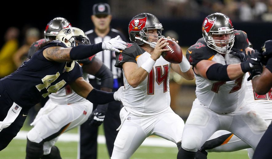 FILE - In this Nov. 5, 2017, file photo, Tampa Bay Buccaneers quarterback Ryan Fitzpatrick (14) scrambles under pressure from New Orleans Saints outside linebacker Hau'oli Kikaha (44) during the second half of an NFL football game in New Orleans. Fitzpatrick and New York Jets' Josh McCown are survivors, aging quarterbacks who keep getting opportunities to prove their worth to NFL teams. The two teams play this week. (AP Photo/Butch Dill, File)