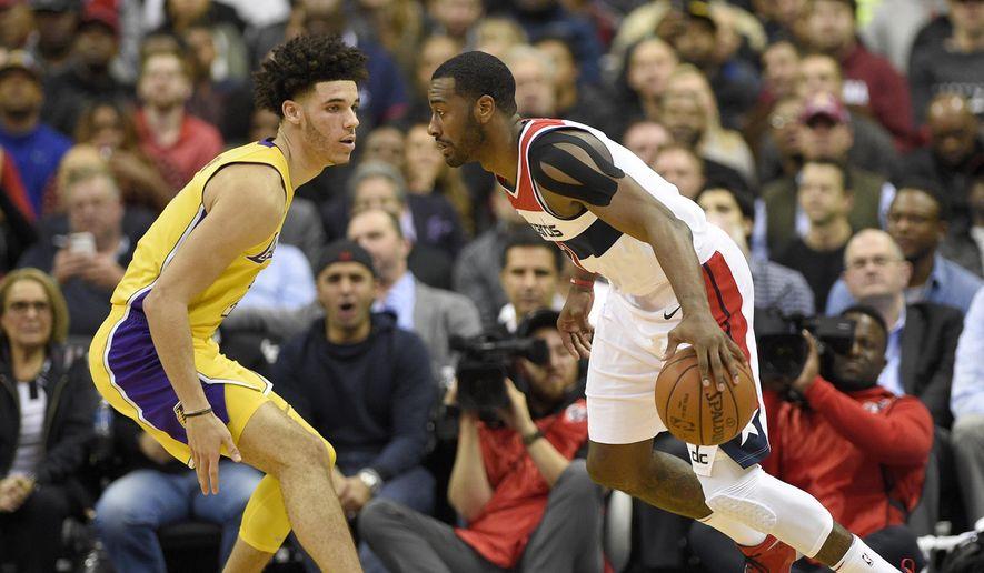 Washington Wizards guard John Wall, right, dribbles against Los Angeles Lakers guard Lonzo Ball during the first half of an NBA basketball game, Thursday, Nov. 9, 2017, in Washington. (AP Photo/Nick Wass)