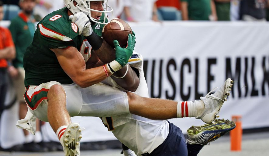 FILE - In this Sept. 23, 2017, file photo, Miami wide receiver Braxton Berrios (8) catches a touchdown pass against Toledo safety DeDarallo Blue (21) during the second half of an NCAA College football game in Miami Gardens, Fla. Berrios has more touchdown catches already this season than in his first three years with the seventh-ranked and unbeaten Hurricanes. He's broken out at the right time for Miami, which takes on No. 3 Notre Dame this weekend in a showdown with national championship implications.  (AP Photo/Wilfredo Lee, File)