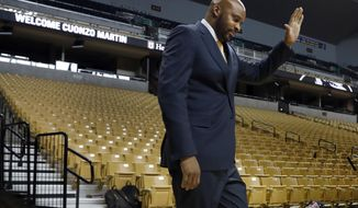 FILE - In this March 20, 2017, file photo, Cuonzo Martin waves as he walks out to be formally introduced as the new basketball coach at Missouri, in Columbia, Mo. Martin is no stranger to Missouri, having grown up just across the Mississippi River in East St. Louis and coached in the state before at Missouri State. Now the former Tennessee and Cal coach is back home with the Tigers, where he thinks the rejuvenated basketball program could be a much-needed source of pride for a Missouri campus still reeling from student protests two years ago. (AP Photo/Jeff Roberson, File)