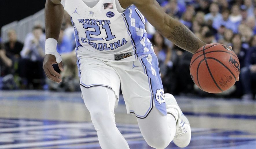 FILE - In this Dec. 17, 2016, file photo, North Carolina's Seventh Woods dribbles against Kentucky during the first half of an NCAA college basketball game in Las Vegas. Ninth-ranked North Carolina has some uncertainty at the point when it opens the season Friday against Northern Iowa. Final Four Most Outstanding Player Joel Berry II is expected to miss the start of the year with a broken bone in his right hand, meaning sophomore Seventh Woods or freshman Jalek Felton are in line for significant minutes. (AP Photo/John Locher, File)