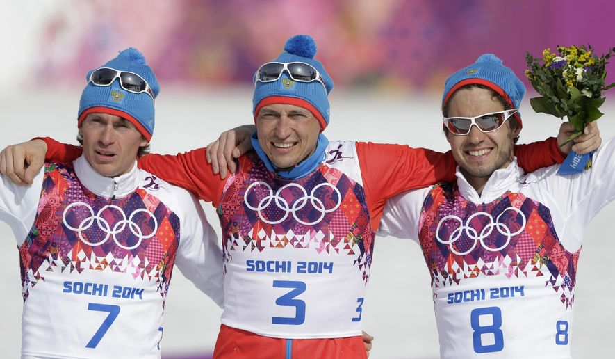 FILE - In this Sunday, Feb. 23, 2014 file photo, Russia's gold medal winner Alexander Legkov is flanked by Russia's silver medal winner Maxim Vylegzhanin, left and Russia's bronze medal winner Ilia Chernousov during the flower ceremony of the men's 50K cross-country race at the 2014 Winter Olympics, in Krasnaya Polyana, Russia.  Four more Russian cross-country skiers have been found guilty of doping at the 2014 Sochi Olympics, it was announced on Thursday, Nov. 9, 2017 including silver medalist Maxim Vylegzhanin.  (AP Photo/Matthias Schrader, file)
