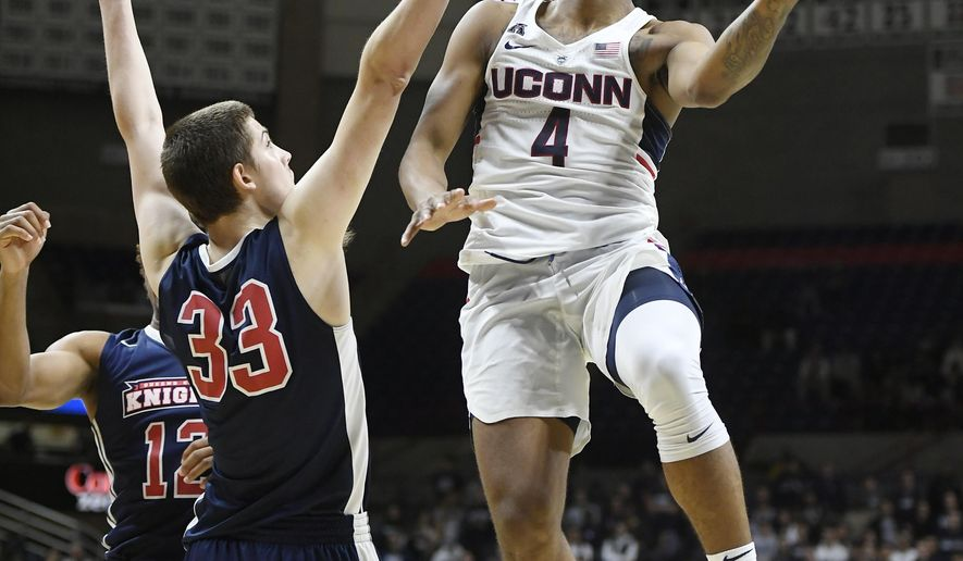 Connecticut's Jalen Adams goes up for a basket as Queens College's Kevin Buron defends in the second half of an NCAA college exhibition basketball game Sunday, Nov. 5, 2017, in Storrs, Conn. (AP Photo/Jessica Hill)