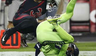 Seattle Seahawks wide receiver Paul Richardson makes the catch as Arizona Cardinals safety Budda Baker, left, defends during the first half of an NFL football game, Thursday, Nov. 9, 2017, in Glendale, Ariz. (AP Photo/Ross D. Franklin)