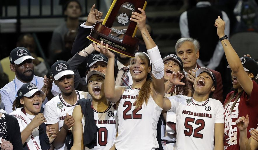 FILE - In this April 2, 2017, file photo, South Carolina forward A'ja Wilson (22) holds up the trophy as she celebrates with teammates after their 67-55 win over Mississippi State in the final of the NCAA women's Final Four college basketball tournament in Dallas. South Carolina won 67-55. After a thrilling Final Four in April that ended with the Gamecocks winning their first national championship, women's college basketball is ready to get started Friday (AP Photo/Eric Gay, File)