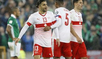 Switzerland's Ricardo Rodriguez celebrates with teammates after the World Cup qualifying play-off first leg soccer match between Northern Ireland and Switzerland at Windsor Park in Belfast, Northern Ireland, Thursday Nov. 9, 2017. (AP Photo/Peter Morrison)
