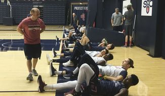 In this Wednesday, Nov. 1, 2017, photo, strength and conditioning coach Steve DiLustro looks over the Saint Mary's basketball team as they stretch in Moraga, Calif. On the floor from front to back are players Cullen Neal, Elijah Thomas, Jock Perry, Malik Fitts, Dan Sheets, Jordan Hunter and Kyle Clark. (AP Photo/Janie McCauley)