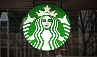 FILE - This Thursday, Jan. 12, 2017, file photo shows a Starbucks logo sign in the window of one of the chain's cafes in Pittsburgh. Starbucks is kicking off its holiday season by offering two holiday drinks for the price of one for three hours a day from Nov. 9 to 13. (AP Photo/Gene J. Puskar, File)