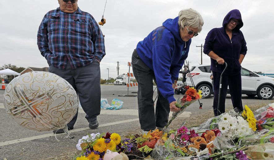 Barbara Solano, center, places flowers at a makeshift memorial for the victims of the First Baptist Church shooting Thursday, Nov. 9, 2017, in Sutherland Springs, Texas. A man opened fire inside the church in the small South Texas community on Sunday, killing more than two dozen and injuring others. (AP Photo/David J. Phillip)