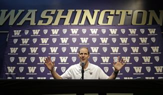 FILE - In this Oct. 17, 2017, file photo, New Washington men's basketball coach Mike Hopkins addresses media members during the team's media day in Seattle. Hopkins can envision a day when the Huskies are back to being a premier program on the West Coast. For now, he will settle for getting the group of Huskies he inherited to play how he wants, beginning with Friday night's opener. (AP Photo/Elaine Thompson, File)