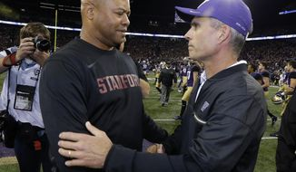 FILE - In this Sept. 30, 2016, file photo, Washington coach Chris Petersen, right, shakes hands with Stanford coach David Shaw after the Huskies  44-6 win in an NCAA college football game in Seattle. Stanford looks to use a short week before hosting No. 9 Washington to put last week's loss at Washington State and last year's defeat against the Huskies in the past. (AP Photo/Ted S. Warren, File)
