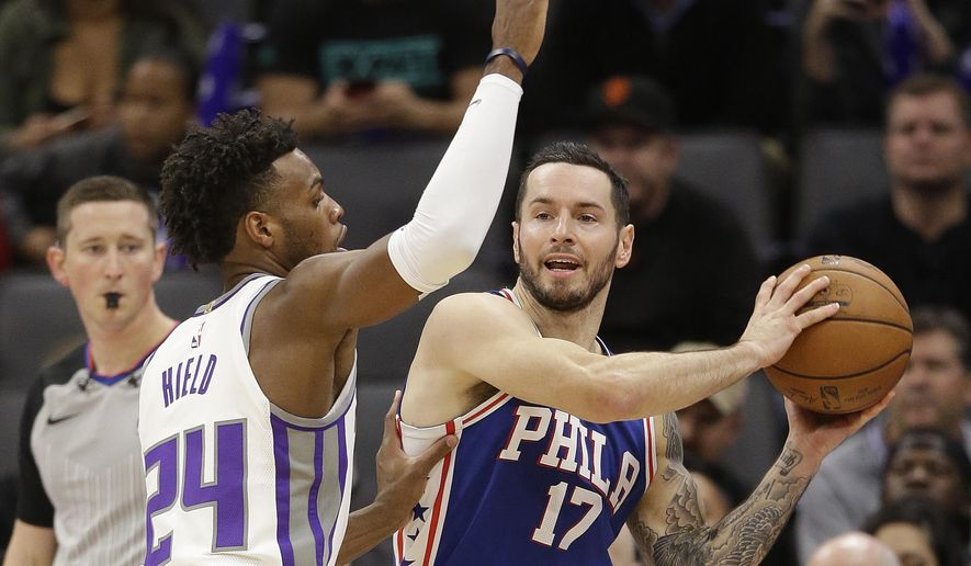 Philadelphia 76ers forward JJ Redick, right, looks to pass as Sacramento Kings guard Buddy Hield defends during the first quarter of an NBA basketball game Thursday, Nov. 9, 2017, in Sacramento, Calif. (AP Photo/Rich Pedroncelli)