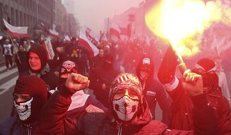 In this Friday, Nov. 11, 2016, file photo, nationalists, burning flares as they march in large numbers through the streets of Warsaw to mark Poland's Independence Day in Warsaw, Poland. Fascists and other far-right extremists are set to assemble in Warsaw for a march that has become one of the largest gatherings in Europe for increasingly emboldened white supremacists. (AP Photo/Czarek Sokolowski, File)