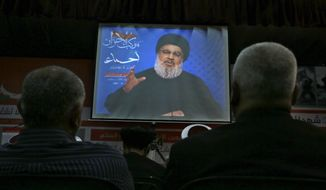 """Hezbollah leader Sheik Hassan Nasrallah, speaks via a video link, during a rally marking Hezbollah Martyr's Day, in a southern suburb of Beirut, Lebanon, Friday, Nov. 10, 2017. Nasrallah said that the country's prime minister is currently detained in Saudi Arabia and that his """"forced"""" resignation is unconstitutional because it was done """"under duress."""" He also said that war with Israel is unlikely. (AP Photo/Bilal Hussein)"""