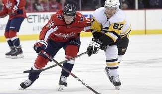 Pittsburgh Penguins center Sidney Crosby (87) battles for the puck against Washington Capitals left wing Jakub Vrana (13), of the Czech Republic, during the first period of an NHL hockey game, Friday, Nov. 10, 2017, in Washington. (AP Photo/Nick Wass)