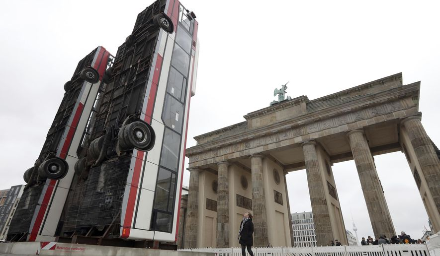Three busses are positioned close to the 'Brandeburg Gate' in Berlin, Germany, Friday, Nov. 10, 2017. Syrian artist Manaf Halbouni placed the three buses upright in the German capital, to remind on the suffering of civilians in the Syrian city of Aleppo. (AP Photo/Michael Sohn)