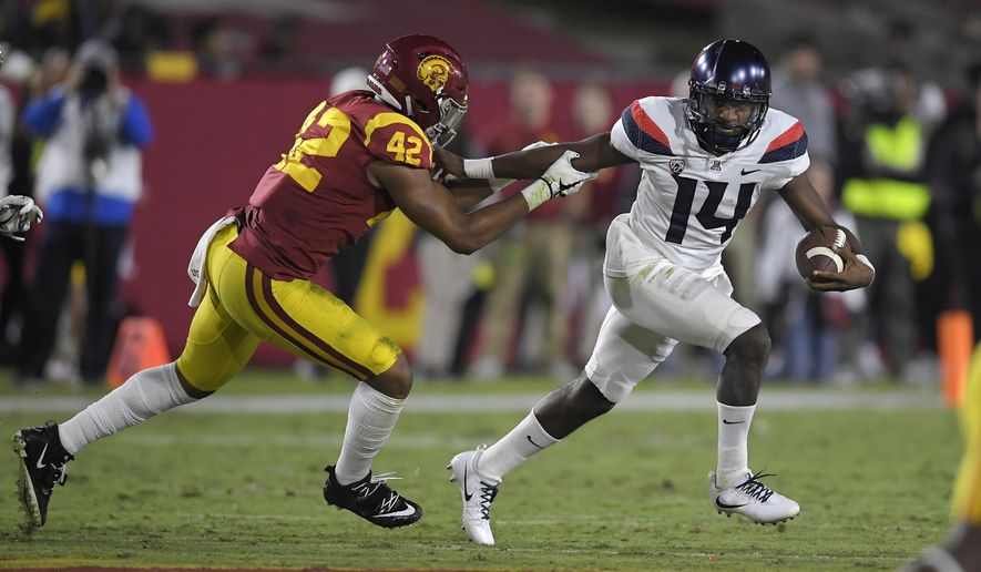 Arizona quarterback Khalil Tate, right, tries to escape a tackle by Southern California linebacker Uchenna Nwosu during the first half of an NCAA college football game, Saturday, Nov. 4, 2017, in Los Angeles. (AP Photo/Mark J. Terrill)