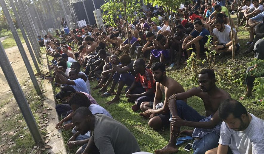 In this Thursday, Nov. 9, 2017 image supplied by Hass Hassaballa, asylum seekers sit on the ground as they refuse to leave the Manus Island detention center in Papua New Guinea. An Australian minister on Friday, Nov. 10 predicted a conflict between Papua New Guinea police and hundreds of asylum seekers who have refused to leave a decommissioned immigration camp where many hold out hope of resettling in the United States. (Hass Hassaballa via AP)