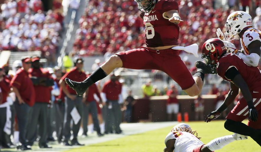 FILE - In this Oct. 7, 2017, file photo, Oklahoma quarterback Baker Mayfield (6) leaps over Iowa State defensive back De'Monte Ruth, bottom, in the second quarter of an NCAA college football game in Norman, Okla. The outright lead in in the Big 12 Conference is on the line when No. 5 Oklahoma hosts No. 8 TCU on Saturday (AP Photo/Sue Ogrocki, File)