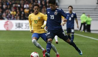 Brazil's Neymar, left, fight s for the ball with Japan's Hiroki Sakai during their international friendly soccer match Brazil against Japan at the Pierre Mauroy stadium in Lille, northern France, Friday, Nov. 10, 2017. (AP Photo/Michel Spingler)