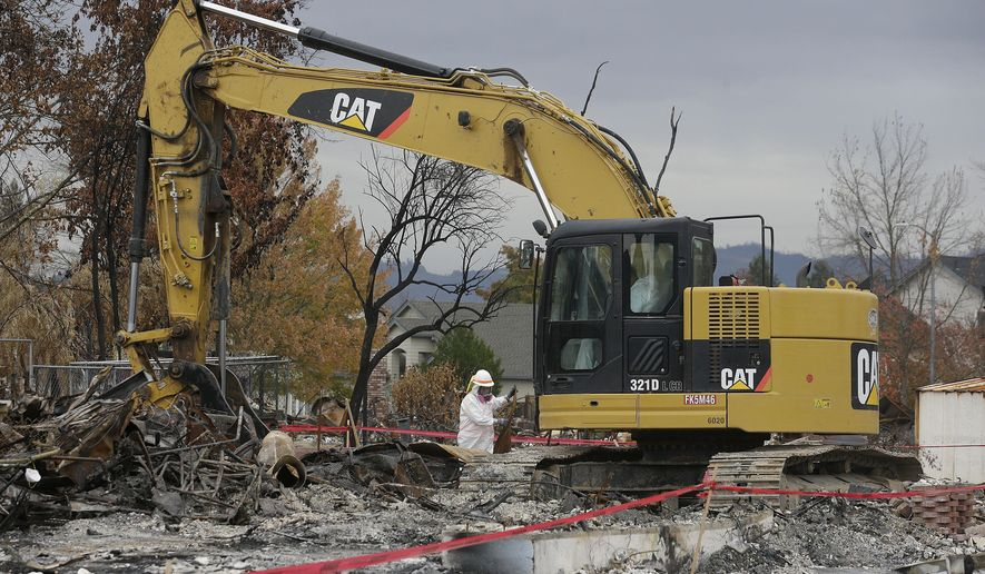 Work crews remove debris a the site of a home destroyed by fires in the Coffey Park area of Santa Rosa, Calif., Wednesday, Nov. 8, 2017. Rumbling front loaders began scraping up the ash and rubble of nearly 9,000 destroyed homes and other structures in Northern California this week as the U.S. Army Corps of Engineers launched a new phase of the largest wildfire clean-up in the state's history. (AP Photo/Jeff Chiu)