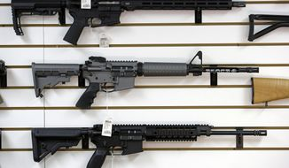 A Ruger AR-15 semi-automatic rifle, center, the same model, though in gray rather than black, used by the shooter in a Texas church massacre two days earlier, sits on display with other rifles on a wall in a gun shop Tuesday, Nov. 7, 2017, in Lynnwood, Wash. Gun-rights supporters have seized on the Texas church massacre as proof of the well-worn saying that the best answer to a bad guy with a gun is a good guy with a gun. Gun-control advocates, meanwhile, say the tragedy shows once more that it is too easy to get a weapon in the U.S. (AP Photo/Elaine Thompson)