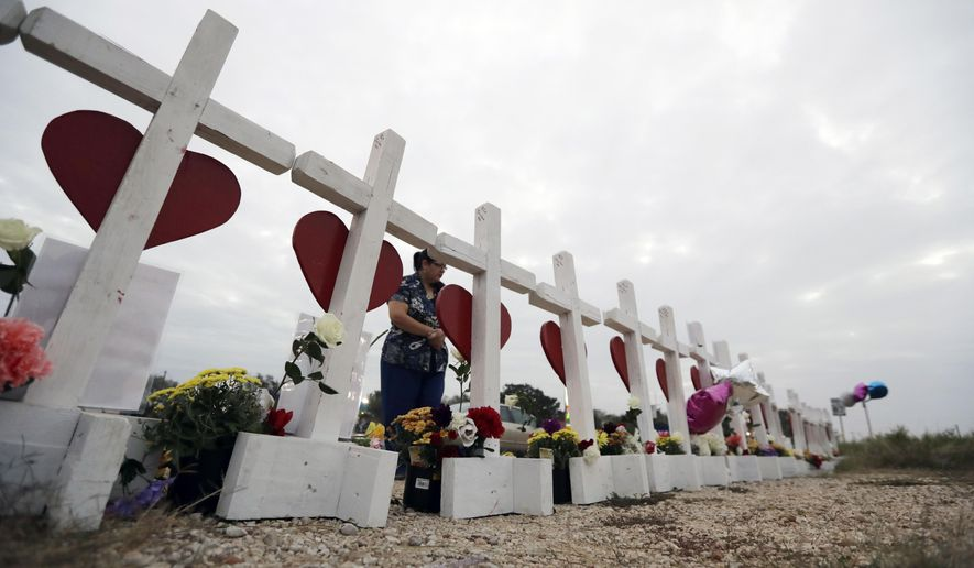 A woman visits a makeshift memorial along the highway for the victims of the church shooting at Sutherland Springs Baptist Church, Friday, Nov. 10, 2017, in Sutherland Springs, Texas. A man opened fire inside the church in the small South Texas community on Sunday, killing more than two dozen. (AP Photo/Eric Gay)