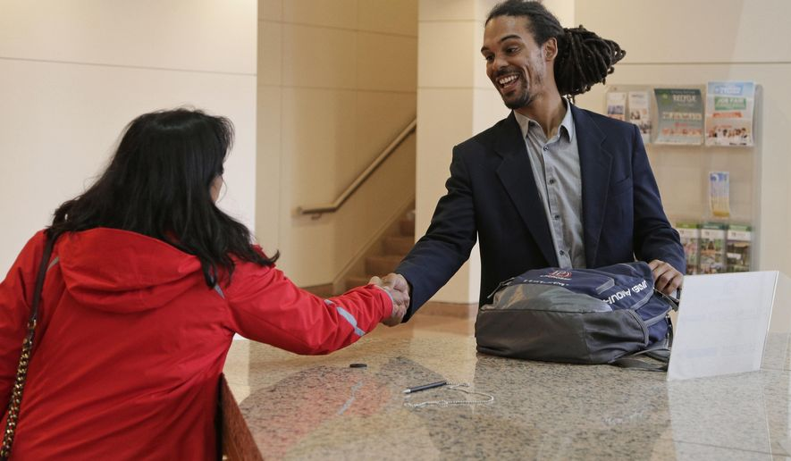 Braxton Winston, right, greets a supporter as he arrives for an orientation meeting at the government center in Charlotte, N.C., Thursday, Nov. 9, 2017. Winston, whose photo during a 2016 protest standing in front of a police line with a fist raised gained national attention, won an at-large seat on Charlotte's city council on Tuesday. (AP Photo/Chuck Burton)