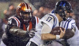 Virginia Tech defender Tim Settle (4) grabs Duke quarterback Daniel Jones (17) from behind in the second half of an NCAA college football game in Blacksburg Va., Saturday, Oct. 28, 2017. Virginia Tech won the game 24-3. (Matt Gentry/The Roanoke Times via AP) ** FILE **
