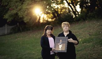 In this Oct. 19, 2017 photo, Sheri McMichael and Melissa Vaccaro pose with a photo of their brother Steven Turner in Harrisburg, Pa. For Vaccaro and her family, Steven's 1981 murder is a wound that never healed, and now it's been opened again by the possibility that Steven's killer could soon gain his freedom.  (James Robinson/PennLive.com via AP)