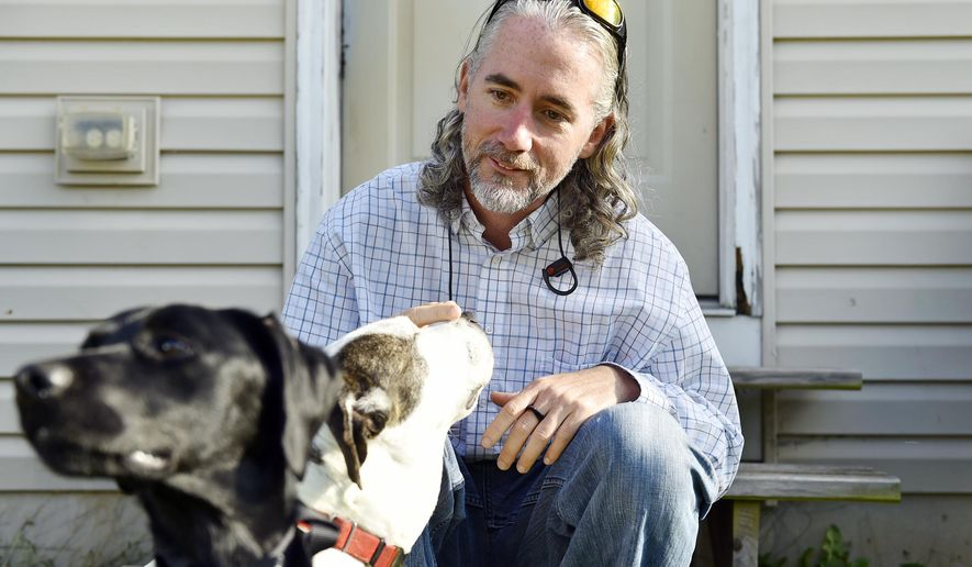 In this Thursday, Nov. 2, 2017 photo, Budhi Blair relaxes with his dogs Ryder, left, and Layla, right, outside Blair's home in Windsor Township, Pa. While serving 9 years in state prison, Blair joined a veterans' program where he learned to train rescue dogs. Blair, who said he endured childhood abuse and has PTSD from his service in Iraq, said working with dogs in the prison program helped him sleep at night and gain a new outlook on life after prison. (Chris Dunn/York Daily Record via AP)