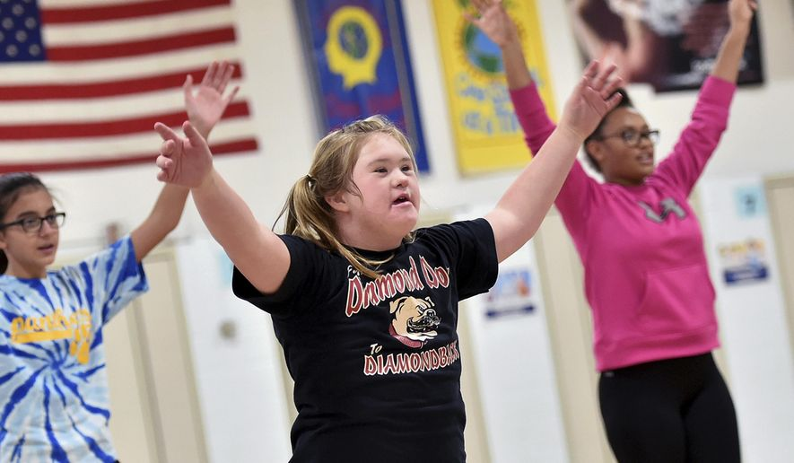 In this Oct. 30, 2017 photo, Northlawn Junior High cheerleading squad member Jacque LeRette, center, runs through routines during practice in Streator, Ill. LeRette really loves cheerleading, so much so she taught herself a number of cheers this summer through watching videos online and practicing on her trampoline at home. Jacque's perseverance paid off, as she was selected for the school's cheerleading squad this year. Jacque, who has Down syndrome, has become an integral member of the team. (Doug Larson/Ottawa Times via AP)