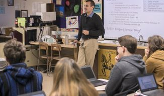 In this Oct. 18, 2017 photo, Collinsville High School Latin teacher James Stark speaks to students in his classroom in Collinsville, Ill. Stark views his students' well being as his top priority. Teaching Latin is somewhere down the list. Stark has been a teacher for three years. At 24 years old, he was named the 2017 Illinois Latin Teacher of the Year by the Illinois Classical Conference. His students say they think of Room 225, the Latin classroom, as a sanctuary. (Derik Holtmann /Belleville News-Democrat, via AP)
