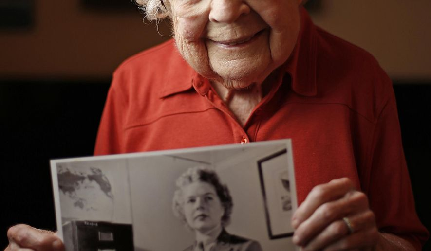 In this Oct. 27, 2017 file photo, Margie McClain, a World War II Marine poses for a photo in  her home in Quincy, Ill. She worked as a journalist during the war. McClain has lived at least nine lives. The 97-year-old has been an advertising representative, a journalist, a college student, a mother and a painter, to name a few. She moves a little slower today than she used to, and she's a little more apt to cry while telling a painful war-time story, but her reflections on her near-century of life are overwhelmingly positive. (Jake Shane/The Quincy Herald-Whig via AP)
