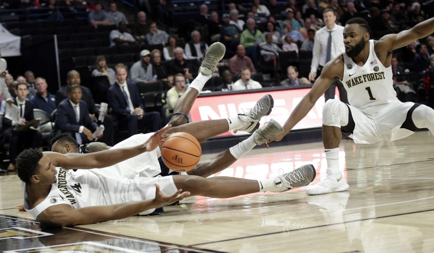 Wake Forest's Doral Moore (4) tries to pass the ball to Keyshawn Woods (1) as he falls out of bound during the second half of an NCAA college basketball game against Georgia Southern in Winston-Salem, N.C., Friday, Nov. 10, 2017. (AP Photo/Chuck Burton)