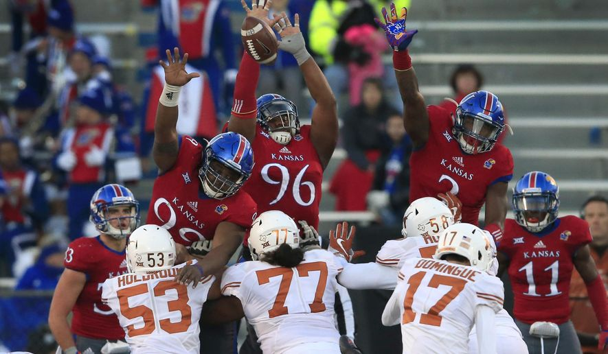 FILE - In this Nov. 19, 2016, file photo, Texas place kicker Trent Domingue (17) kicks a point after touchdown over Kansas defensive tackles Daniel Wise (96), DeeIsaac Davis (99) and defensive end Dorance Armstrong Jr. (2) during the second half of an NCAA college football game in Lawrence, Kan. The Jayhawks head to Texas this week looking for a repeat of their shocking win in 2016.  (AP Photo/Orlin Wagner, File)