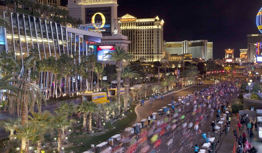 FILE - In this Dec. 4, 2011 file photo, runners stream southward on Las Vegas Boulevard during the Rock 'n Roll Las Vegas Marathon in Las Vegas. More than 40,000 people will run on Sunday, Nov. 12, 2017, under the watchful eyes of snipers and surrounded by other law-enforcement safety measures during the Las Vegas Rock 'n' Roll Marathon, the first large-scale outdoor event the city's hosting since a gunman killed 58 people gathered at a country music festival last month. (AP Photo/Julie Jacobson, File)