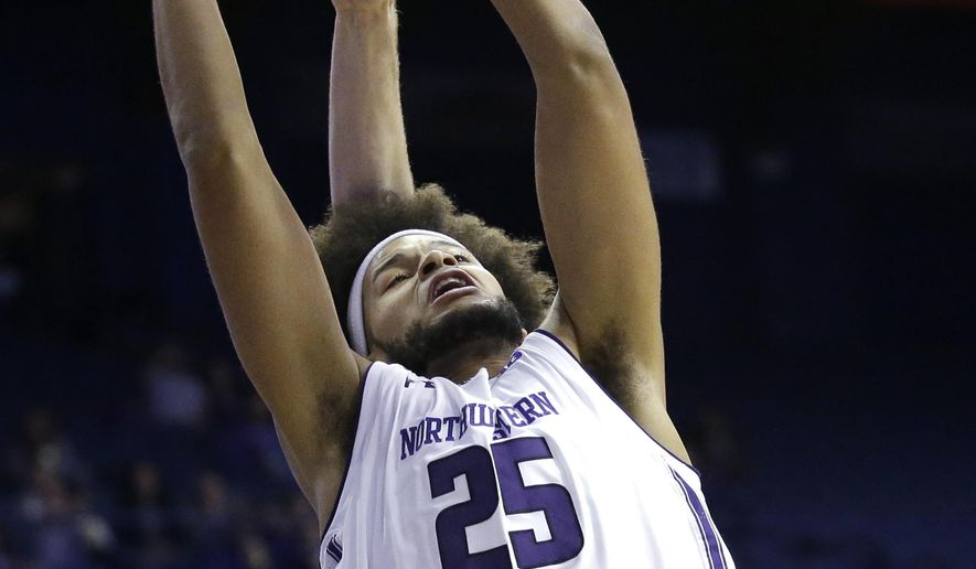 Northwestern center Barred Benson rebounds a ball against Loyola (Md.) forward Brent Holcombe during the first half of an NCAA college basketball game Friday, Nov. 10, 2017, in Rosemont, Ill. (AP Photo/Nam Y. Huh)