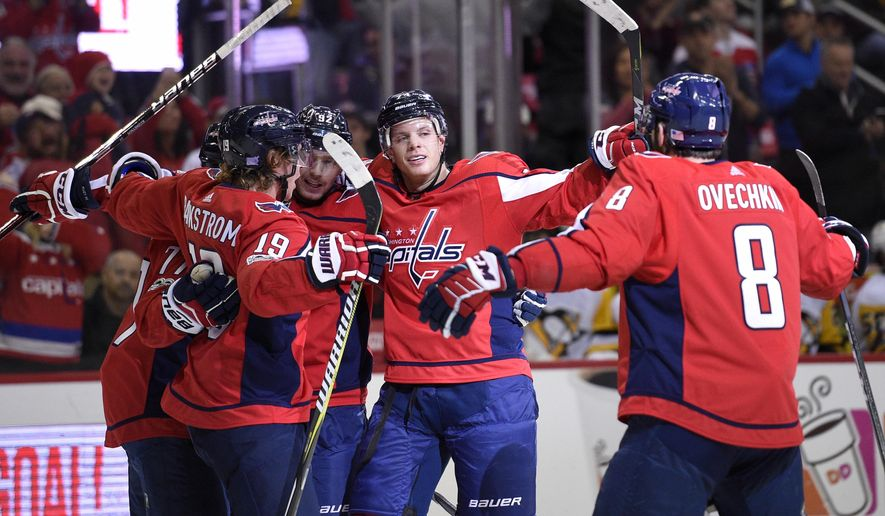 Washington Capitals defenseman John Carlson, second from right, celebrates his goal with left wing Alex Ovechkin (8), of Russia, center Nicklas Backstrom (19), of Sweden, and others during the first period of an NHL hockey game against the Pittsburgh Penguins, Friday, Nov. 10, 2017, in Washington. (AP Photo/Nick Wass)